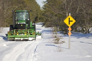 front view of a trail groomer clearing off a snowy snowmobile trail