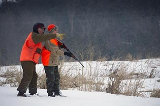 A man helps a boy with hunting in a snow-covered field.