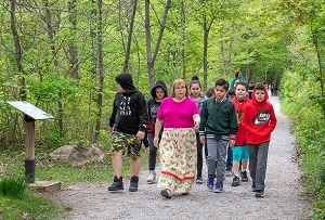 group of young people on on a nature hike on a trail at Sanilac Petroglyphs Historic State Park