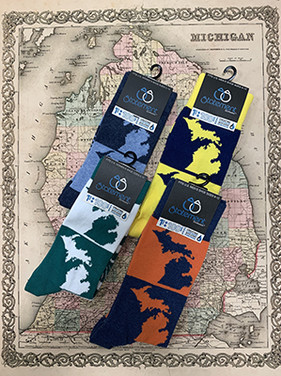 Four pairs of socks photographed on a historic map of Michigan background.