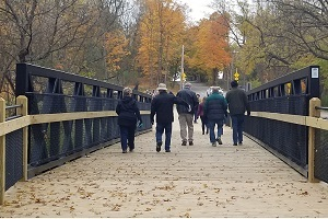 back view of people walking along the Old Orchard Pathway