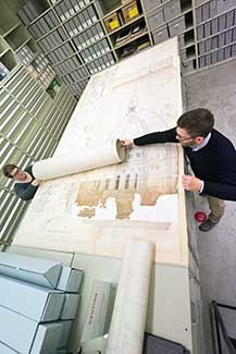 Two people spread out architectural drawings of the state capitol.