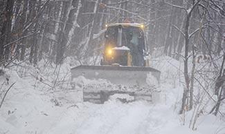 A bulldozer moves along a snowmobile trail in Marquette County.
