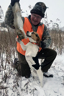 A man holds a rabbit he shot up and away from his dog.