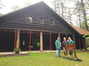 Three adults stand in front of the Hartwick Pines Memorial Building
