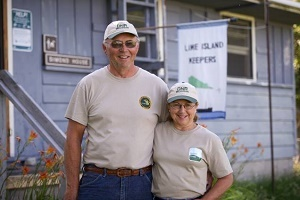 Older man and woman wearing DNR hats and shirts, serving as Lime Island Recreation Area campground hosts, 2018