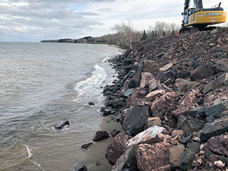 A front end loader sits along a repaired section of Lake Superior beachfront.