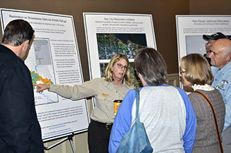 A U.S. Fish and Wildlife Service worker talks with people about recovery projects.