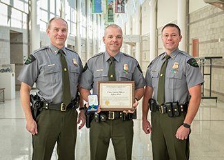 A lauded officer is pictured with two of his superiors.