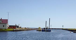A dredging rig works to remove stamp sands from the Grand Traverse Harbor in summer.