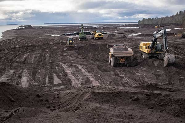 Heavy equipment operators work to move stamp sands away from Lake Superior.