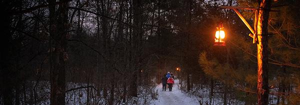 Snowshoe hikers on lantern-lit trail