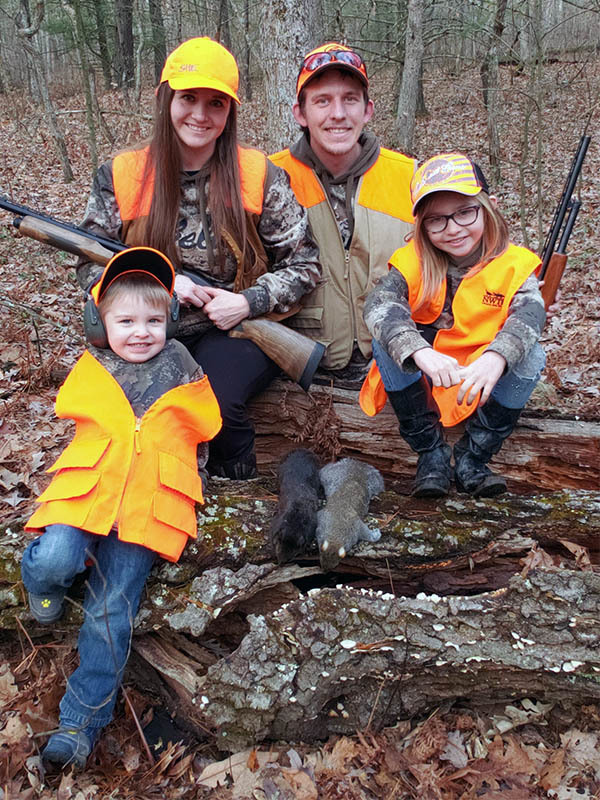 Two children and their parents are pictured after a successful squirrel hunt.