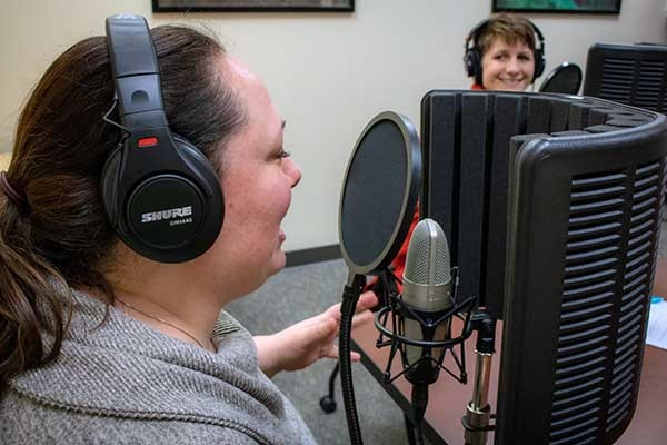 Podcast hosts record an episode in a makeshift studio.