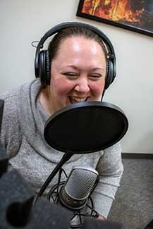 Holly Vaughan laughs during a podcast recording.