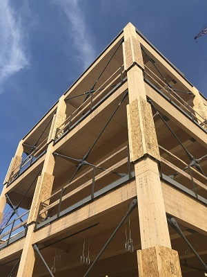 looking up at the corner of a multistory, mass timber building under construction, blue sky above