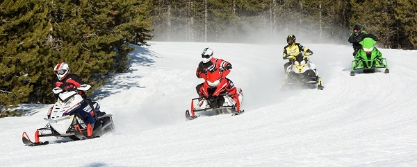 four snowmobilers coming around a curve in the trail