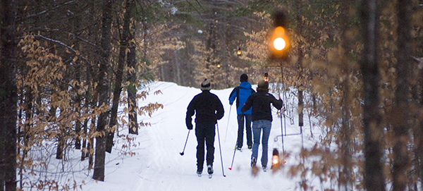 cross-country skiers on trail with lanterns lit
