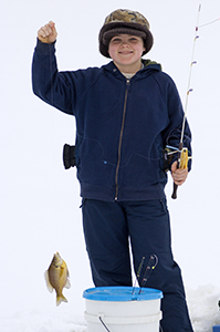 boy ice fishing holding pole with fish on it
