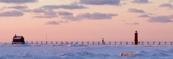 frozen waves, clouds and pink sunset surround Grand Haven Lighthouse and pier