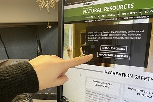 "Someone's finger pointing to the ""replace lost certificate"" button on the DNR recreational safety webpage"