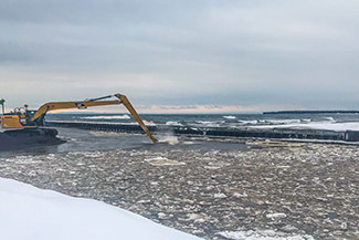 A backhoe is used to clear stamp sands from the Grand Traverse Harbor.