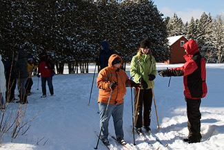 Skiers stopped along a trail on a sunny afternoon are shown.
