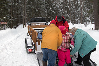 A Ski for Light participant is helped toward the ski trails.
