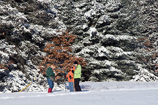 Skiers work their way across a snowy field in Roscommon County.