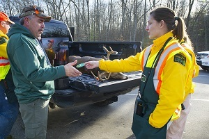 A DNR employee (right) at a deer check station gives a hunter a deer cooperator patch