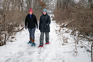 Two women enjoy a snowshoe hike at the Island Lake Recreation Area in Livingston County.