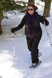 A woman with snowshoe and trekking poles moves along a snowshoe trail.