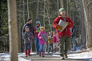 Hartwick Pines State Park interpreter Craig Kasmer leads a group of kids and adults through the forest, ready to tap maple trees for syrup