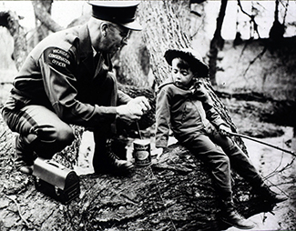 In a historic photo, a conservation officer shows a young boy how to tie a fishing knot.