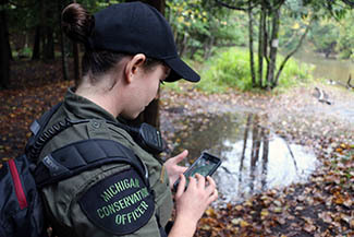 A female conservation officer is shown on a fishing patrol, using technology to check property lines.