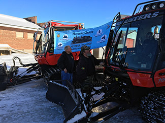 Schoolcraft County Motorized Trail Association members attach a celebration banner between trail groomers.