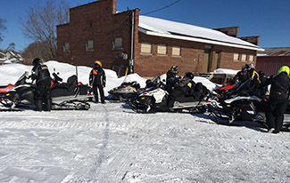A photo of snowmobilers gathered for the Haywire Grade's 50th anniversary celebration is shown.