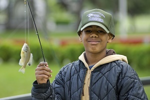 young boy wearing a jacket and cap, holding a fish he caught