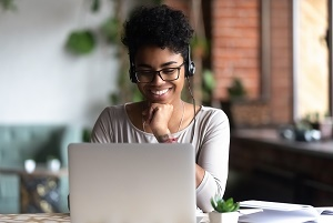 Smiling woman wearing glasses and headphones, in front of a laptop