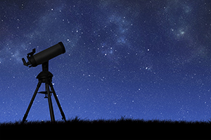 telescope in shadow against a star-filled sky