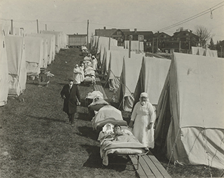 A nurse is shown standing outside a field hospital tent.