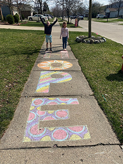 """Two children on a sidewalk are shown, the artists of a stylized chalk drawing of the word """"Hope."""""""