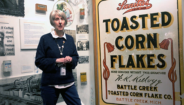 A history educator stands before a Kellogg's display at the Michigan History Center.