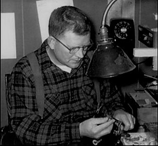 A historic photo shows Clarence Roberts tying flies.