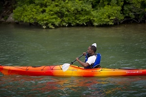side view of a man kayaking