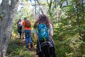 View from the back, hikers with backpacks spaced out along a trail at Wilderness State Park