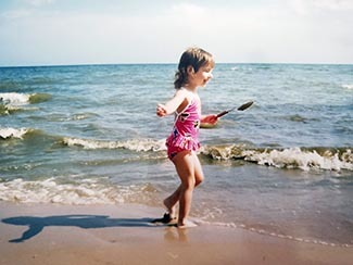 A picture of the author as a young girl along a beach is shown.