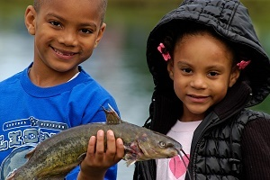 smiling young boy and girl holding a fish