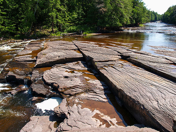 A view is shown looking upstream on the Presque Isle River at Porcupine Mountains Wilderness State Park.