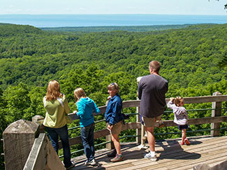 A family is shown enjoying the overlook at Summit Peak at Porcupine Mountains Wilderness State Park.